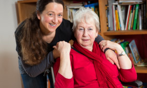caregiver and elder woman in wheelchair smiling