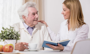caregiver reading book for her patient
